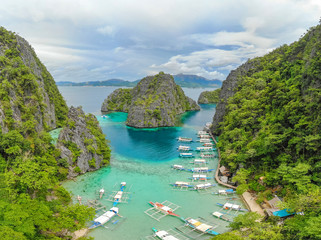 Blue crystal water in paradise Bay with boats on the wooden pier at Kayangan Lake in Coron island, Palawan, Philippines.