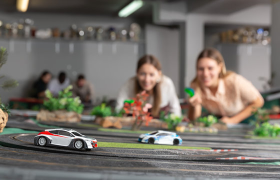 Emotional portrait of two women holding remote control and playing slot car racing