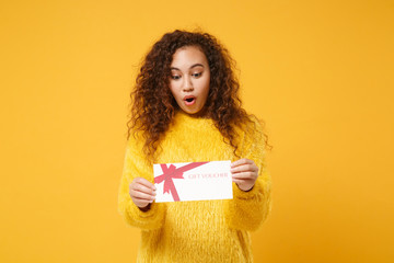 Shocked young african american girl in fur sweater posing isolated on yellow orange background...