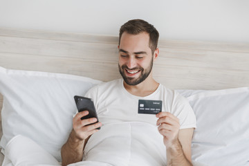 Calm young bearded man lying in bed with white sheet pillow blanket in bedroom at home. Male spend time in room with mobile phone credit card. Rest relax good mood lifestyle concept Mock up copy space