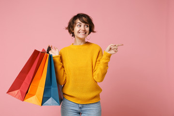 Smiling young brunette woman girl in yellow sweater posing isolated on pink background. People lifestyle concept. Mock up copy space. Hold package bag with purchases after shopping point finger aside. Wall mural