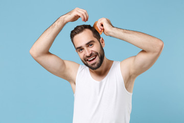 Close up bearded young man 20s years old in white shirt hold comb hair isolated on blue pastel wall background, studio portrait. Skin care healthcare cosmetic procedures concept. Mock up copy space.