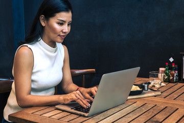 Asian woman tapying on a laptop. Empty space on the wall