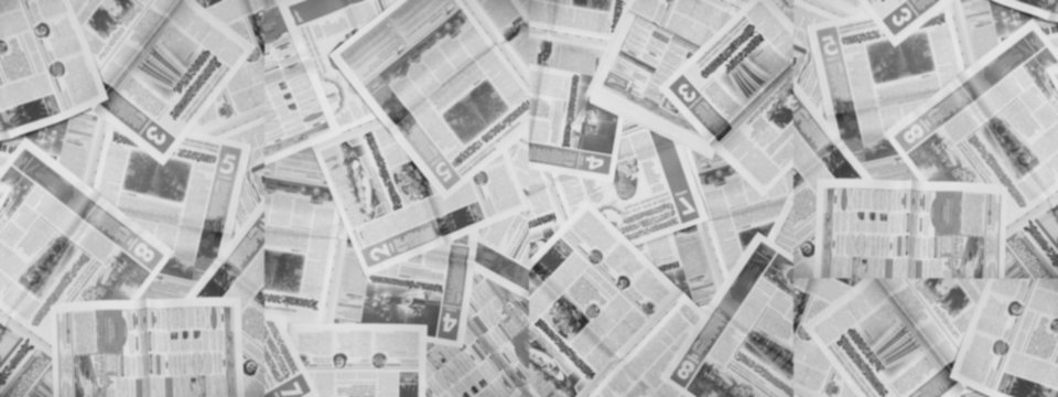Long horizontal banner with lots of old newspapers on horizontal surface. Background texture, top view, blurred. Concept for news and information - could be used for web design or advertisement