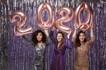 women in fancy sparkling dresses posing isolated over vibrant purple violet silver background....