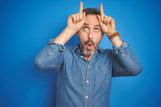 Handsome middle age senior man with grey hair over isolated blue background doing funny gesture with finger over head as bull horns