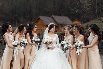 Photo of the bride and bridesmaidswith wedding bouquets. Wedding day after wedding ceremony. Happy girls at their best friend's wedding. Beautiful bride with her friends. Autumn wedding