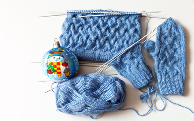 Winter needlework. Hand knitting warm mittens and hats as a gift for Christmas. The process of circular knitting on five needles. Mohair blue yarn and christmas ball. Flat lay, close-up, copy space