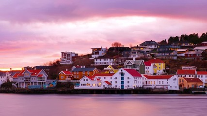 Wall Mural - Kristiansund, Norway. View of city center of Kristiansund, Norway during the cloudy morning at sunrise with colorful sky. Time-lapse of port with historical buildings, zoom in
