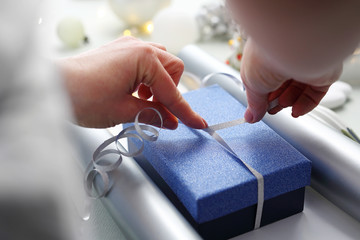 Christmas presents. Woman wraps a present under the Christmas tree. Christmas composition in blue...