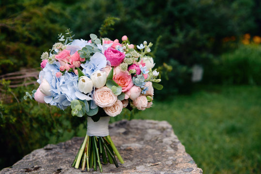 Close up of bridal bouquet of pink roses and blue hydrangea flowers on stone background outdoors, copy space. Wedding concept
