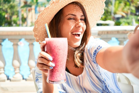 Beutiful woman sitting at pool bar on hotel resort drinking healthy smoothie and taking selfie using smartphone
