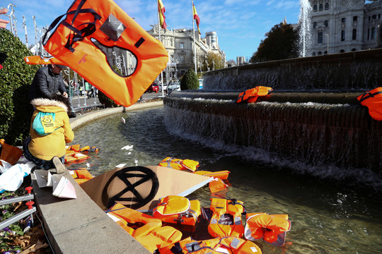 Members of Extinction Rebellion group throw life jackets into Cibeles Fountain as they stage a protest during the U.N. climate change conference in Madrid