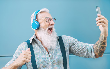 Happy senior man taking selfie while listening music with headphones - Hipster mature male having fun using mobile smartphone playlist apps - technology and elderly lifestyle people concept Papier Peint