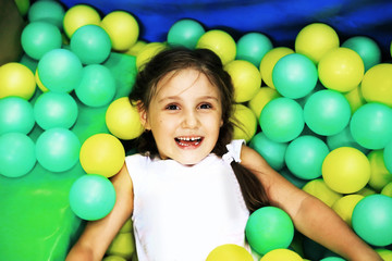 little girl with colorful balloons on the Playground