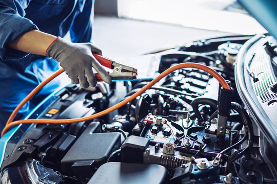 Mechanic man maintenance jump battery charging the engine a vehicle car hood, Safety inspection test engine before customer drive on a long journey, transportation repair garage service center