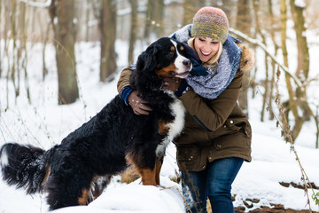 Woman walking her dog in the winter and both explore the snow together