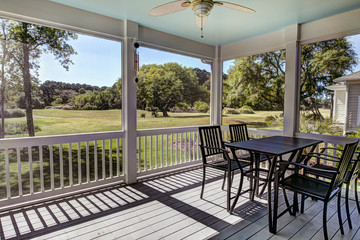 Three season screen porch with view out onto golf course and park.