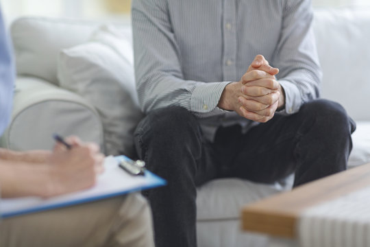 Psychologist taking notes during psychotherapy session with man