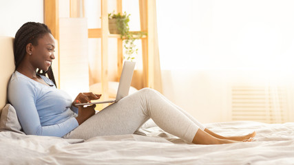 Wall Mural - Happy African American Woman Working On Laptop In Bedroom, Panorama