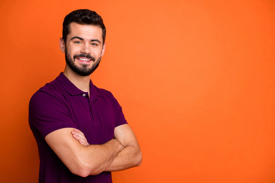 Photo of cheerful positive handsome man with arms crossed standing near empty space looking at you isolated orange vibrant color background