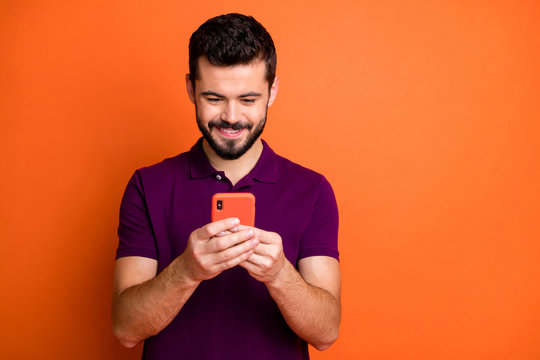 Portrait of cheerful positive guy use his cell phone chatting with social media friends comment reposts wear modern youth outfit isolated over vibrant color background