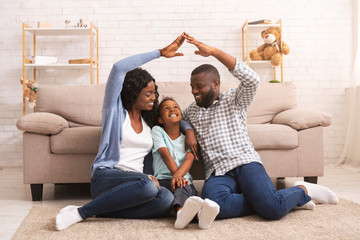 Black parents making symbolic roof of hands above little daughter's head