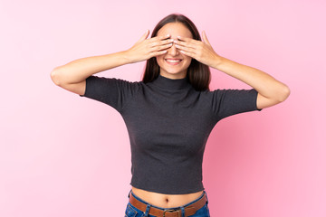 Young girl over isolated pink background covering eyes by hands
