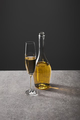 glass and bottle of sparkling wine on grey
