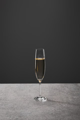 one glass of sparkling wine for celebrating christmas on grey