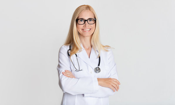 Smiling medical physician doctor posing on grey background