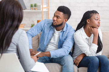 Indifferent black spouses sitting on couch at marital therapist's office.