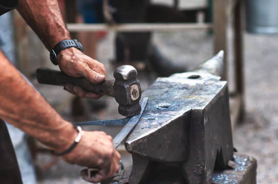 An artisan blacksmith knocks with a hammer on iron to shape