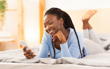 Wall Mural - Black Girl Using Smartphone Lying In Bed At Home