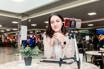 A young woman blogger in a shopping center works at a laptop, conducts live broadcasts, records videos, communicates with followers of her social networks