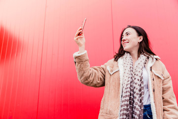 Young woman blogger stands in front of the red wall, holds a mobile phone in her hands and takes pictures, takes a selfie or communicates