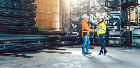 Handshake of worker and customer in warehouse