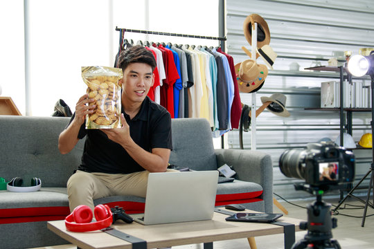 Online blogger, a young Asian man, uses a camera to record live video vlog to present products via social media. Online shopping concept
