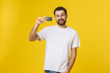 Happy smiling young man showing credit card isolated on yellow background