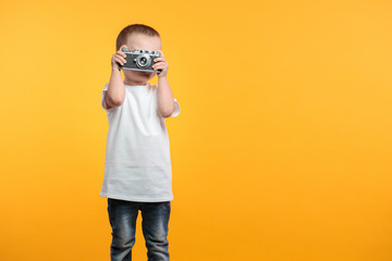 Boy taking a picture with a retro camera over yellow background