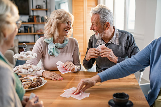 Happy mature couple talking while playing cards with friends at home.