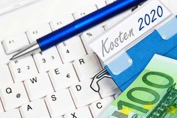 Euro banknote and keyboard and German: Costs 2020
