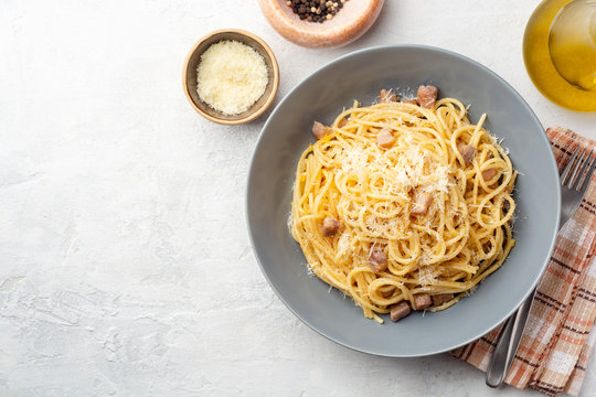 Classic spaghetti pasta carbonara with pancetta, egg yolk and parmesan cheese on concrete background. Top view, copy space.