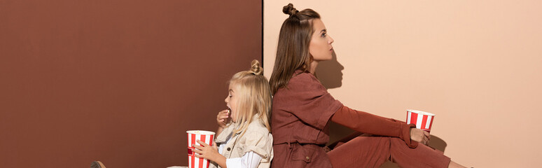 panoramic shot of daughter eating popcorn and mother on beige and brown background