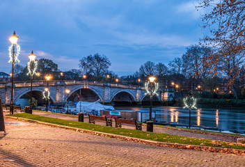 Richmond bridge over Thames river illuminated at dusk and Christmas decorations on the riverside early in the morning at blue hour in London