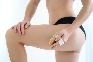 Fototapeta Woman brushing skin buttocks and butt with a dry wooden brush to prevent and treatment cellulite and body problem after shower at home. Skin health