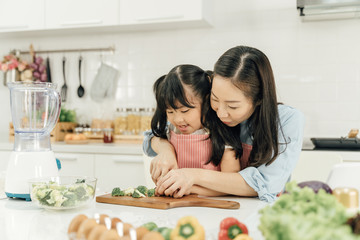 Young asian family cooking food in kitchen.Cute little girl and her beautiful parents are cutting vegetables and smiling while cooking in kitchen at home.Happy family in the kitchen concept.