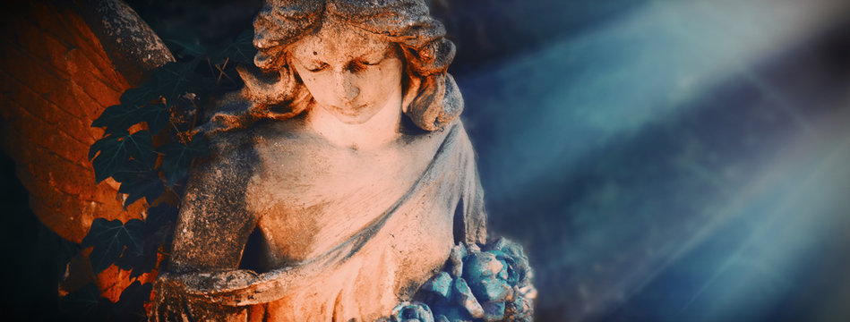 Ancient statue of beautiful angel in the sunlight