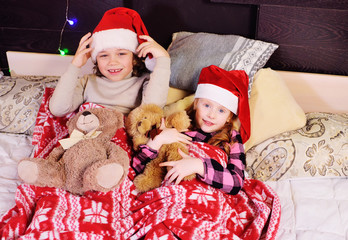 children-a boy and a girl in red socks in the style of Santa and hats lie on the bed under a blanket waiting for the celebration of Christmas and gifts.