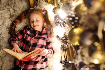a little girl with red hair is lying under a Christmas tree, reading a book of fairy tales and smiling.